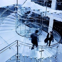 stock-photo-9440135-businessman-walking-down-modern-glass-staircase large